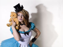Alice look a like. Young woman with a top hat and white and blue faery tale dress Royalty Free Stock Photography