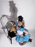 Alice look a like. Young woman with a top hat and white and blue faery tale dress Stock Photography