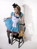 Alice look a like. Young woman with a top hat and white and blue faery tale dress Stock Images