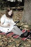 Alice som läser en bok arkivfoton