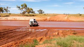 Alice Springs, Australia - December 30, 2008: Off-road car crossing the river on the country road, Australian Northern territory royalty free stock image