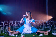 Alice trinkt Tee von einer kleinen Schale in einem Kreis von magischen Tieren Stockbild