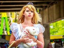 Alice in Wonderland. Attractive female model in Alice costume, with white rabbit, in wonderland stock photos