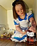 Alice. In wonderland giant magical dressup girl child drink Royalty Free Stock Images