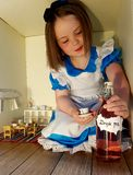 Alice in wonderland. Giant Alice in wonderland magical dressup girl child drink storybook fairytale royalty free stock image