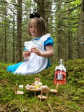 Alice. In wonderland giant magical dressup girl child forrest enchanted storybook fairytale teaparty bottle Stock Photography