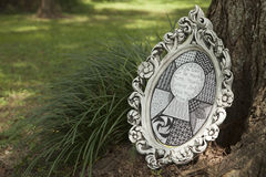 Alice in Wonderland quote. White Antique Framed pen and ink quote from Alice in Wonderland leaning against a tree surrounded by grass and greenery royalty free stock images