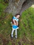 Alice in wonderland. Sleeping  storybook fairytale girl child dressup tree Stock Photos
