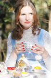 Alice in Wonderland Tea party. Beautiful girl drinking tea like Alice in Wonderland royalty free stock image
