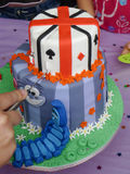 Alice in Wonderland theme cake. Slicing beautiful multi colored birthday cake Stock Photo