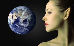 Alien. Profile of a beautiful female alien and the planet earth Stock Photography