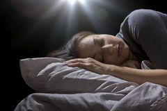 Alien Abduction. Creepy glowing orb hovering over a woman sleeping in bed Stock Image