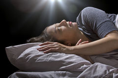 Alien Abduction. Creepy glowing orb hovering over a woman sleeping in bed Stock Photos