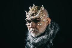 Alien, demon, sorcerer makeup. Senior man with white beard dressed like monster. Demon on black background, copy space. Man with thorns or warts in fur coat royalty free stock image