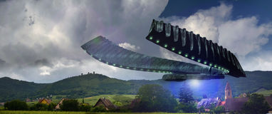 Alien invasion. A giant alien spaceship over a french village in alsace Royalty Free Stock Image