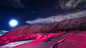 Alien landscape. Below a starry night sky with the moon. image could have come from another planet but is due to a red lantern shining on the snow in arctic stock photography