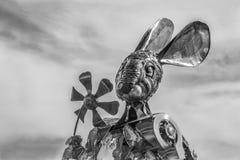Alien Rabbit. Metal rabbit sculpture holding flower Stock Photos