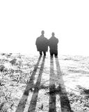 Alien Shadows. A picture of two people standing with the early morning shadows casting long legs across a field Royalty Free Stock Photography