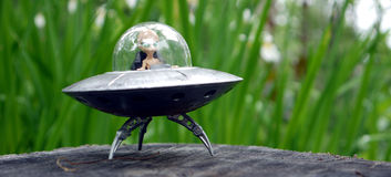 Alien Space Craft. Little green man from Mars in his alien flying saucer U.F.O, landed in a suburban garden Royalty Free Stock Images