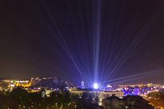 UFO with light rays landing in a city. Alien spaceship landing in a city enviroment. UFO concept with bright light beams in the sky stock photo