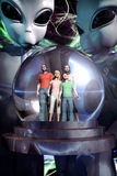 Alien ufo abduction. Greay aliens abduct a human family in 3d Stock Illustration