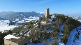 Alifornitoren Marche Italië - San Severino - Middeleeuwse toren in de sneeuw - bewegende hommel luchtvideo stock video