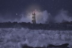 Alight beacon in a stormy sea at night. River mouth pier and alight beacon in a stormy sea at night royalty free stock photo