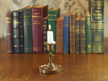 Alight candle. Old candlestick and alight candle with vintage books row Royalty Free Stock Photography