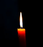 Alight candle. Over the black background Stock Image