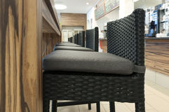 Aligned high rattan chairs in front of wood table Stock Photography
