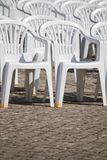 Aligned white plastic chairs Stock Photos