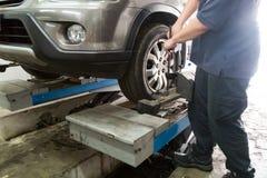 Aligner dell'automobile della riparazione del meccanico sulla ruota di automobile Fotografia Stock