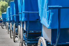 Alignment of blue wheelchairs in front of the swimming pools in. Lourdes, FRANCE, June 22, 2017 - Alignment of blue wheelchairs in front of the swimming pools in Stock Photo