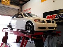 Alignment on Bmw white. White Bmw on alignment rack getting alignment done Stock Photos