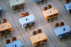 Alignment of restaurant tables and chairs. Looking down on an outdoor restaurant. Alignment of tables covered with orange and blue oilcloth and chairs Royalty Free Stock Image