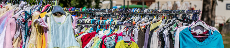 Alignment of second hand baby and children clothing to recycle. Alignment of second hand baby and children clothing displayed on rack per size at outdoor flea stock photo