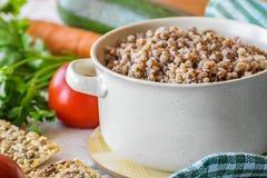 Aliment biologique normal Gruau bouilli de sarrasin dans un pot Légumes crus frais Photographie stock libre de droits