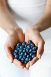 Aliment biologique sain La femme remet complètement des myrtilles mûres douces photos stock