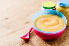 Aliment pour bébé : bol coloré de purée de fruit sur le bois Image stock