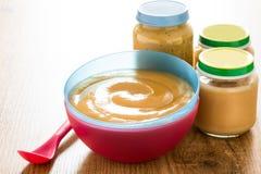 Aliment pour bébé : bol coloré de purée de fruit sur le bois Images libres de droits