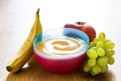 Aliment pour bébé : bol coloré de purée de fruit sur le bois Photos libres de droits