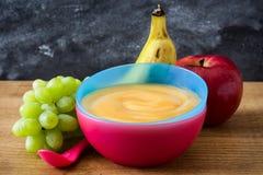 Aliment pour bébé : bol coloré de purée de fruit sur le bois Photos stock