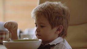 Aliment pour bébé, consommation de chéri Petit type appréciant son gruau L'enfant drôle mangent du gruau avec du lait clips vidéos