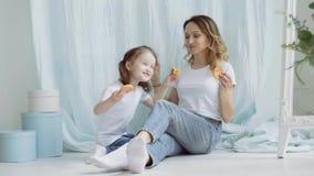 Alimentação da mamã e da menina cookies Uma mulher com uma filha pequena está sentando-se no assoalho filme
