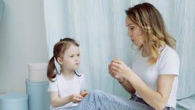 Alimentação da mamã e da menina cookies Uma mulher com uma filha pequena está sentando-se no assoalho Uma mãe nova filme