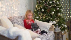 Alimentación de la niña Toy Kitten cerca del árbol de navidad metrajes