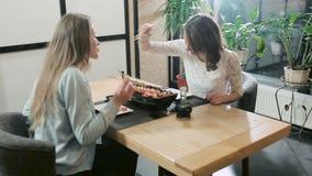 Alimentación de las muchachas en restaurante japonés metrajes
