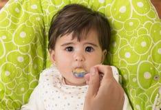 Alimentación de un bebé precioso lindo Imagen de archivo libre de regalías