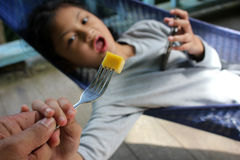 Alimentación del papá un mango a su hija que el ` s interesó solamente con el teléfono Foto de archivo libre de regalías