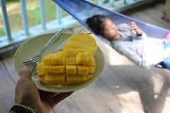Alimentación del papá un mango a su hija que el ` s interesó solamente con el teléfono Fotos de archivo libres de regalías